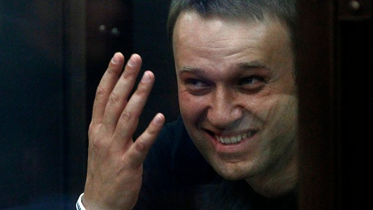 Russian opposition leader Alexei Navalny gestures inside a glass-walled cage as he attends a court hearing in Kirov
