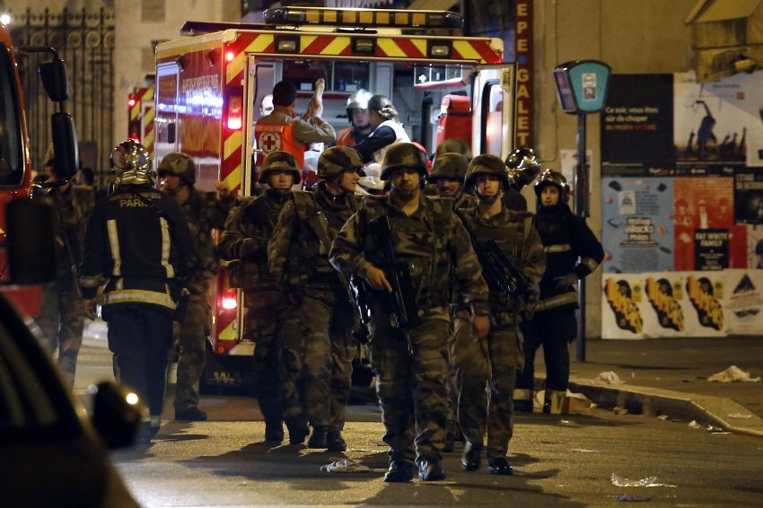Soldiers walk in front of an ambulance as rescue workers evacuate victims near La Belle Equipe, rue de Charonne, at the site of an attack on Paris on November 14, 2015 after a series of gun attacks occurred across Paris as well as explosions outside the national stadium where France was hosting Germany. More than 100 people were killed in a mass hostage-taking at a Paris concert hall and many more were feared dead in a series of bombings and shootings, as France declared a national state of emergency. AFP PHOTO / PIERRE CONSTANT