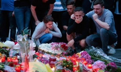 People lay flowers and candles outside the OEZ shopping center the day after a shooting spree left nine victims dead on July 23, 2016 in Munich, Germany. According to police an 18-year-old German man of Iranian descent shot nine people dead and wounded at least 16 before he shot himself in a nearby park. For hours during the spree and the following manhunt the city lay paralyzed as police ordered people to stay off the streets. Original reports of up to three attackers seem to have been unfounded. The shooter's motive is so far unclear.