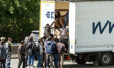 Migrants climb in the back of a lorry on the A16 highway leading to the Eurotunnel on June 23, 2015 in Calais, northern France. Some of the thousands of illegal immigrants camped in Calais and desperately trying to cross the Channel to reach Britain took advantage of a protest by French sailors blocking access roads to the Channel Tunnel on June 23 to climb onto stationery vehicles, said an AFP reporter on the scene.  AFP PHOTO / PHILIPPE HUGUEN