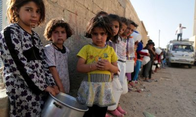 "Syrian children wait in line to collect a free ""Iftar"" meal in the northern city of Raqqa during the Muslim holy month of Ramadan on July 14, 2013. The new head of the Syrian National Coalition Ahmad Jarba has backed calls for a truce from UN chief Ban Ki-Moon during the holy month of Ramadan. During Ramadan, Muslims the world over gather with family over festive meals after sunset when they can break the dawn-to-dusk fast. AFP PHOTO/MEZAR MATAR"