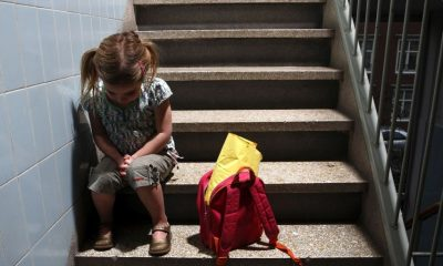THE HAGUE - A little girl sits on concrete stairs, with her backpack next to her, bowing her head, afraid. ANP ROOS KOOLE