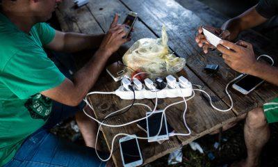 Menekültek töltik telefonjaikat a szerbiai Kanjizában (Fotó: AFP)