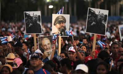 People hold images of Cuba's late President Fidel Castro as they wait for the arrival of the caravan carrying Castro's ashes in Santiago de Cuba, Cuba, December 3, 2016.                 REUTERS/Carlos Barria - RTSUJ3E