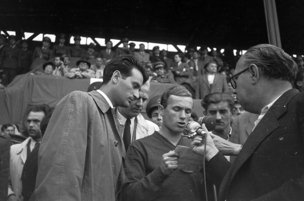 Lakat Károly a mérkőzés előtt felolvas egy nyilatkozatot(?) a mikrofonba, mellette balra Szepesi György riporter, közöttük félig takarva Gulyás Gyula riporter, 1949 / Fotó: Fortepan.hu