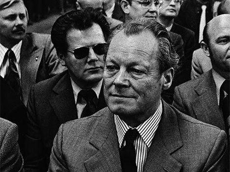 Elől a kancellár, mögötte a Stasi embere - fekete napszemüvegben, ahogy kell /Fotó: Alchetron.com