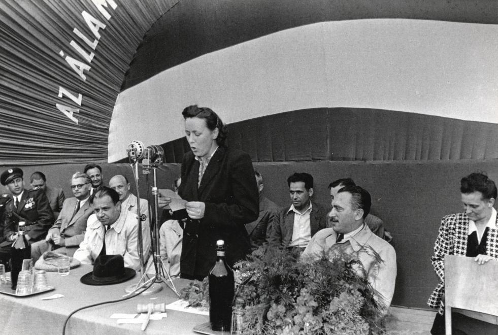 Átadják az ÁVH csapatzászlóját (1949), szónokol a zászlóanya Farkas Mihályné (született Käthe Rüdiger) mellette balra Farkas Mihály, mögötte szemüveggel Zöld Sándor, félig takarva Donáth Ferenc. Jobbra a virágcsokor mögött Péter Gábor / Fotó: Fortepan.hu