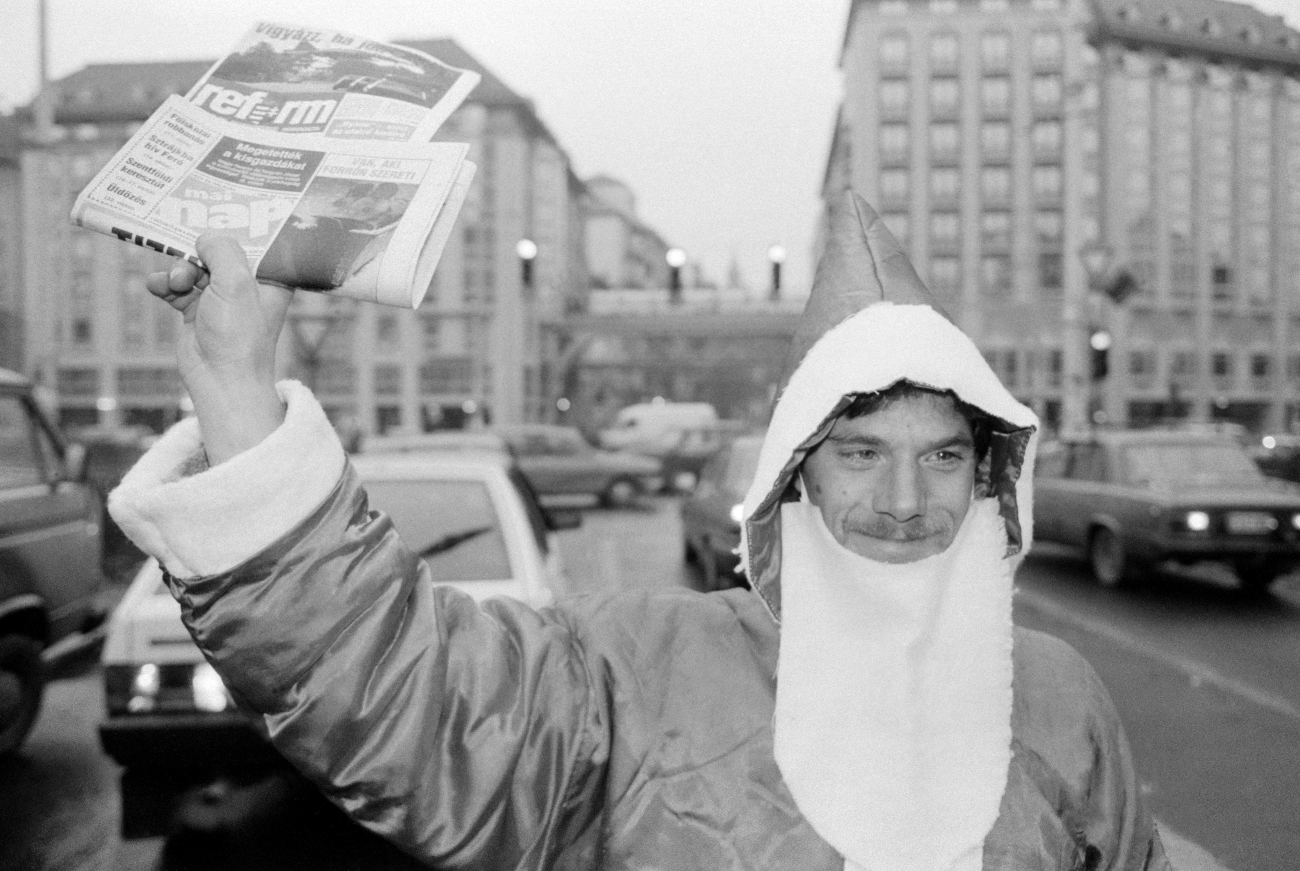 Budapest, 1990. december 5. Utcai újságárus Télapó jelmezben árulja a lapokat az autósoknak a Kálvin téri keresztezõdésben / MTI Fotó: Kleb Attila