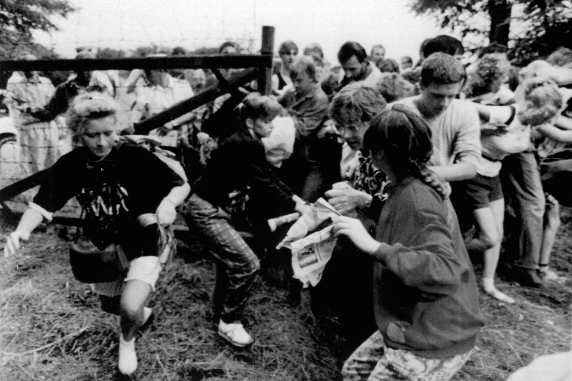 A több hete Magyarországon tartózkodó NDK-beli állampolgárok egy, mintegy háromszáz fõs csoportja tör át a magyar-osztrák határon lévõ mûszaki határzár kapuján, 1989. augusztus 19-én amikor a Sankt Margarethen és Sopron közötti úton a Páneurópai piknik alkalmából, a kijelölt átkelõt ideiglenesen megnyitották a Nyugatról érkezõk elõtt. Összesen 350 NDK-beli állampolgár menekül át Ausztriába / MTI/REUTER