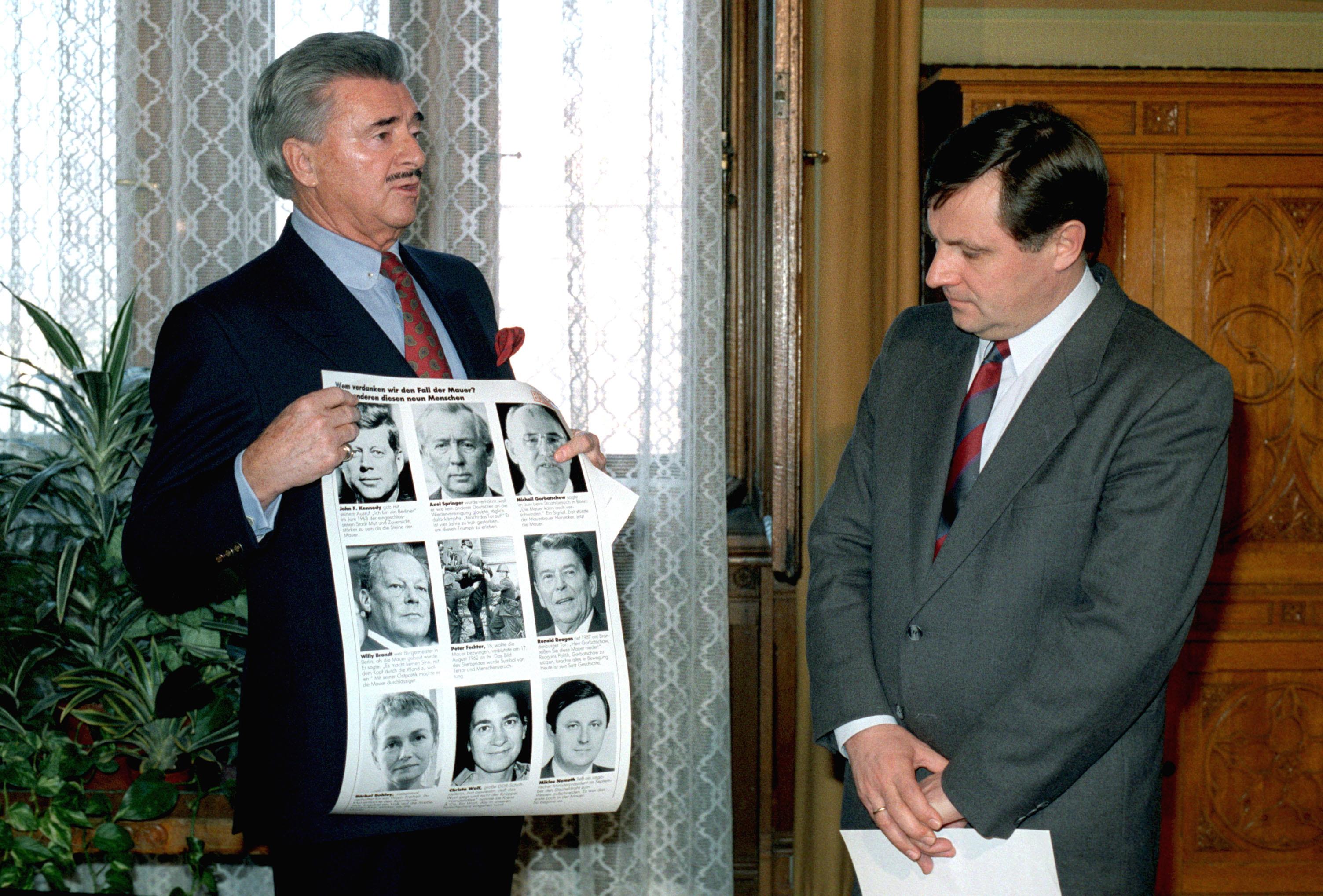1989. november 24. Josef von Ferenczy átadja Németh Miklós miniszterelnöknek azt a tablót, melyet a német Bunte magazin jelentetett meg azokról a politikusokról, akik hozzájárultak a Berlini Fal lebontásához. A tablón John F. Kennedy, Ronald Reagan, Mihail Gorbacsov, Willy Brandt és több más neves személyiség mellett Németh Miklós fotója is helyet kapott. / Fotó: MTI