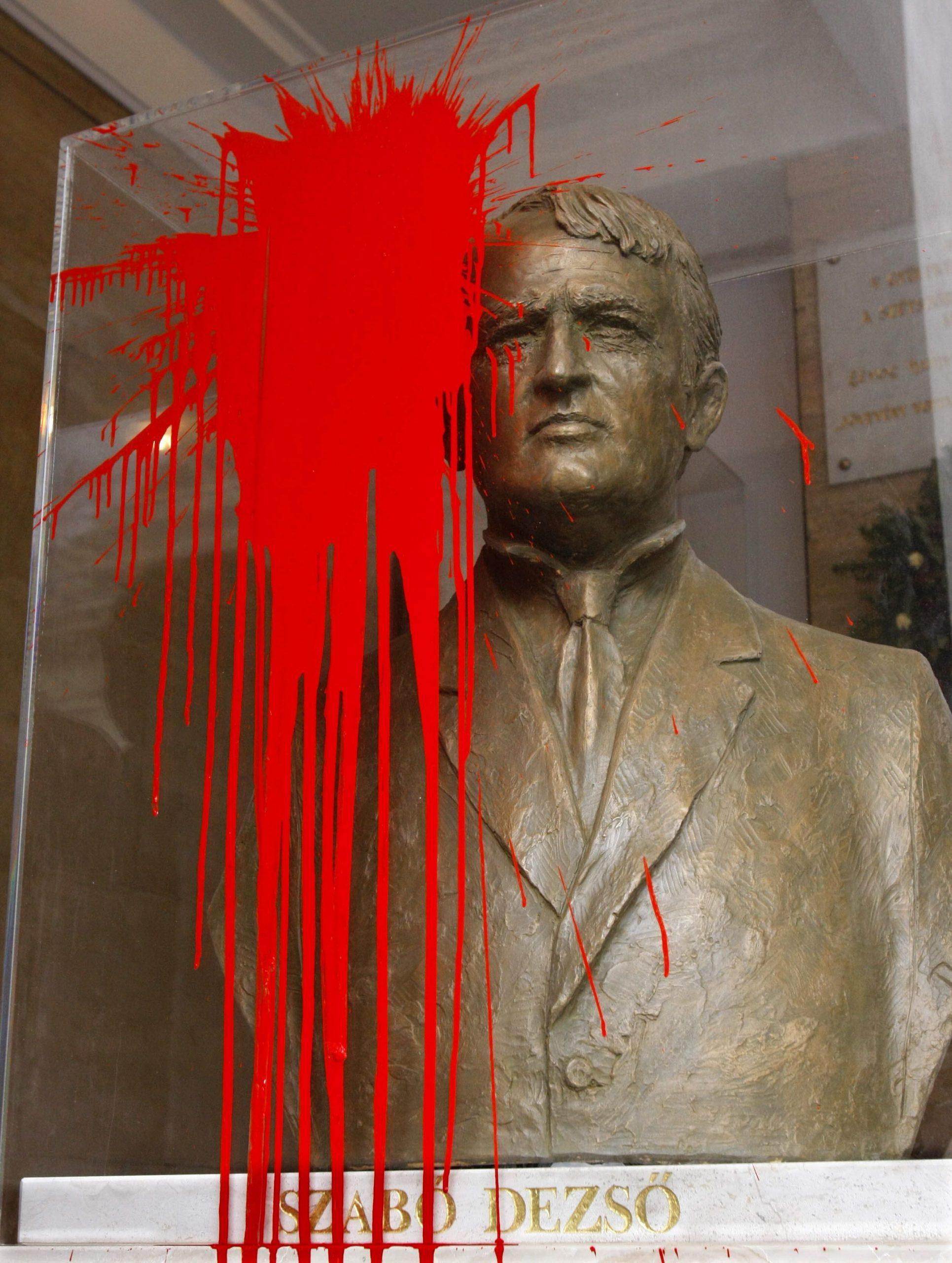 Holtában sem nyugodhat. 2009-ben vörös festékkel öntötték le Szabó Dezső szobrának üvegburáját / Fotó: MTI