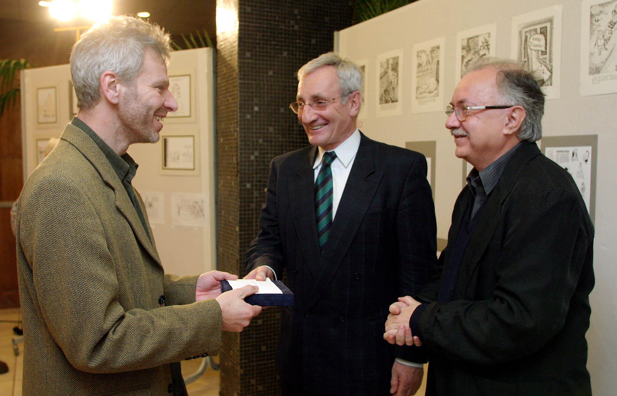 Büszkék lehettek rá. Pápai Gábor átveszi a díjat Eötvös Pál és Farkasházy Tivadar újságírótól, a bírálóbizottság tagjaitól / Fotó: MTI