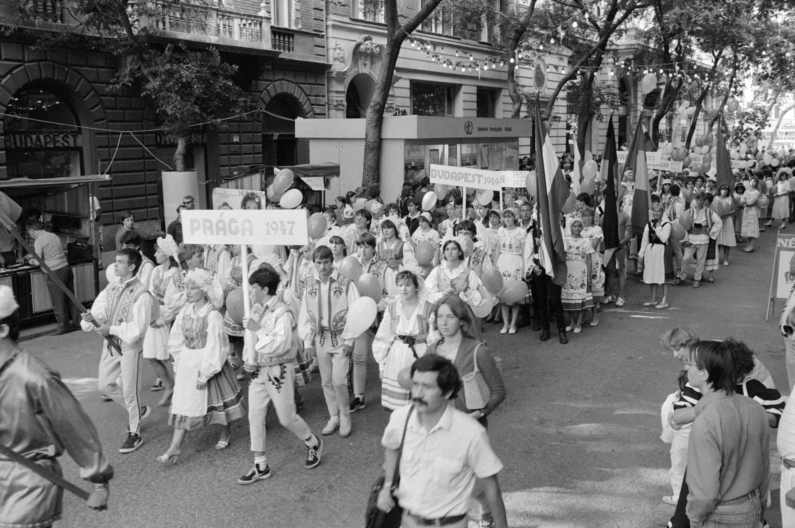 """A korábbi Világifjúsági Találkozók (VIT) """"színpompás"""" ruháiba öltözött fiatalok 200 tagú csoportja vonul fel a VIT-centrumban. 1985 / Fotó: MTI"""