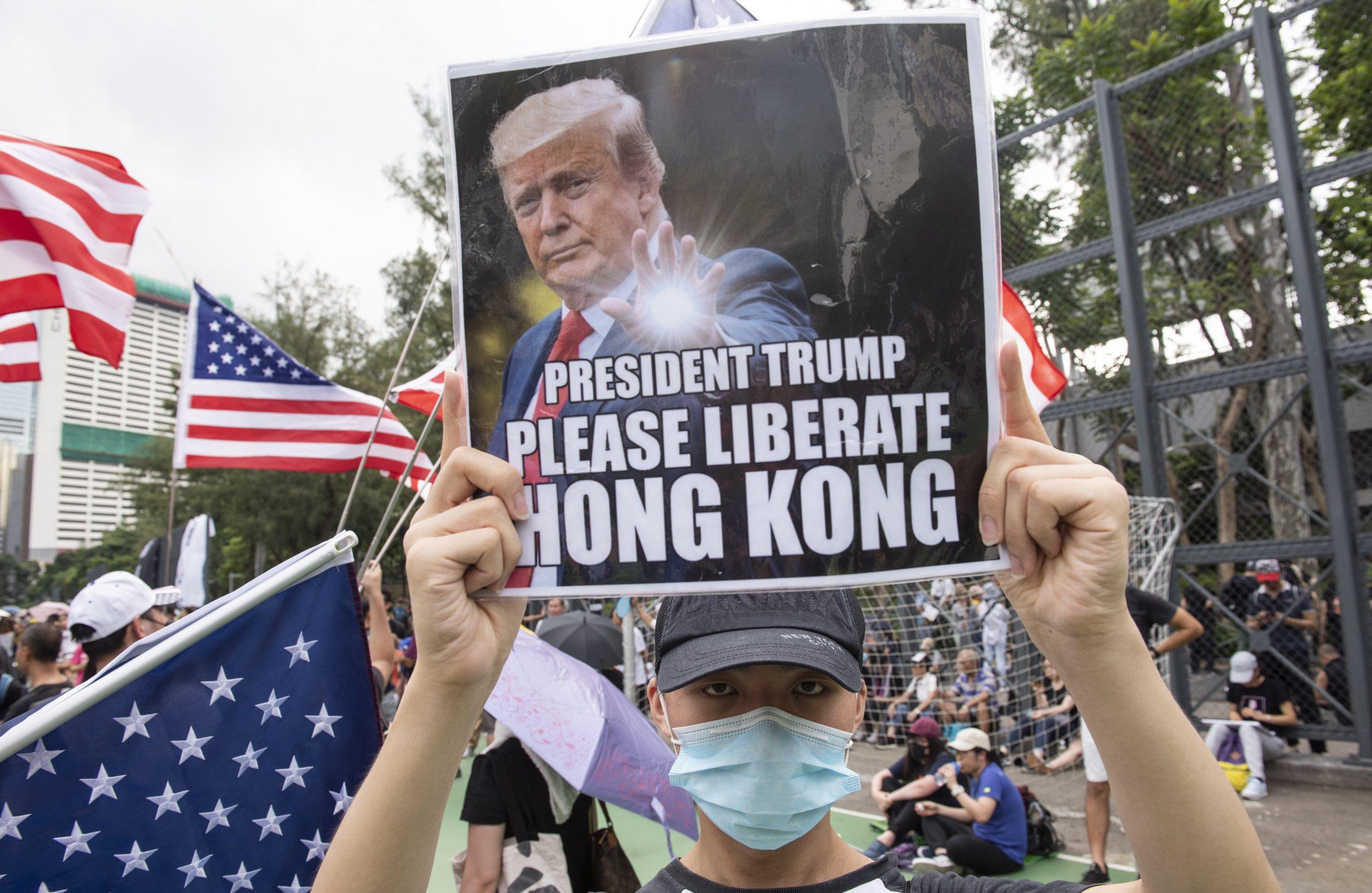 Az amerikai elnököt ábrázoló, Trump elnök, kérlek, szabadítsd fel Hongkongot jelentésű felirattal ellátott fényképet mutat fel egy tiltakozó / Fotó: MTI/EPA