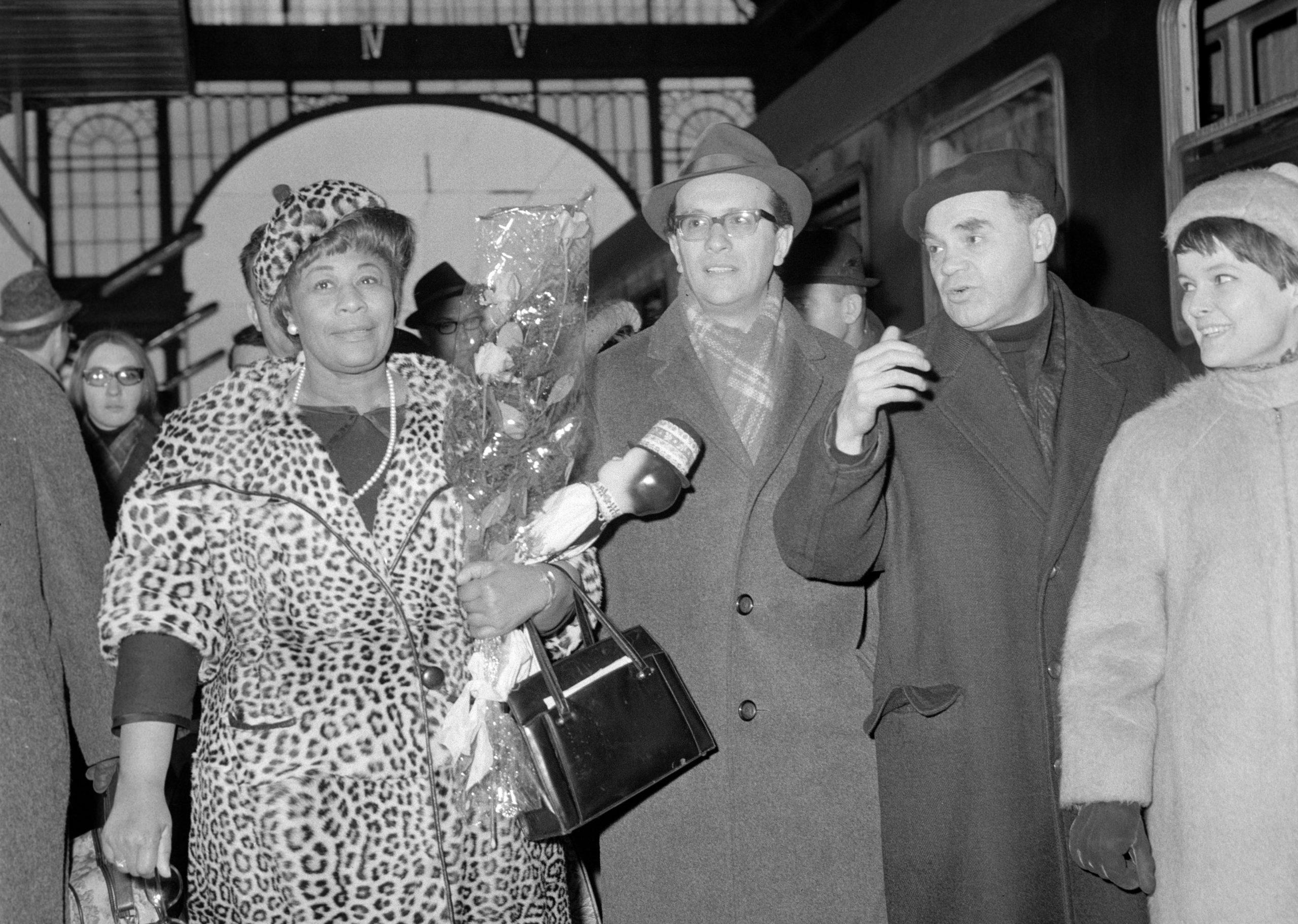 Jazz-legenda és a kommunista hálózat emberei. Ella Fitzgerald világhírû jazzénekesnõt Keszler Pál, az Országos Rendezõ Iroda (ORI) (szemüvegben, kalapban), Bánki László, a Nemzetközi Koncertiroda (sapkában) vezetõje és Poór Klári riporternõ fogadták a Keleti pályaudvaron. / Fotó: MTI