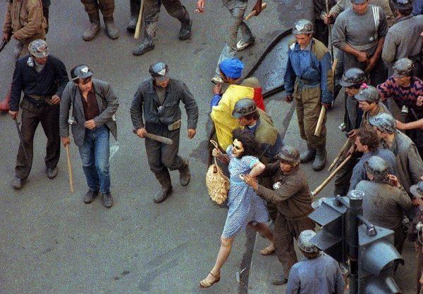 Bányászok egy csoportja egy tüntetővel erőszakoskodik Bukarest központjában az 1990. júniusi bányászjárás idején. Forrás: Andrei Iliescu, AFP/MTI