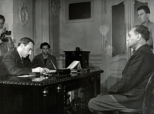 Péter Gábor (balra) itt éppen Szálasit hallgatja ki az Andrássy út 60-ban lévő irodájában. Fotó: Fortepan