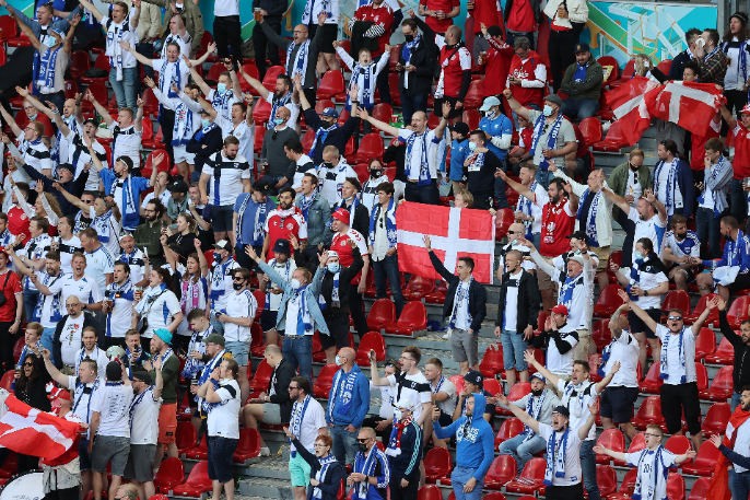 Dán zászlót lobogtatva éltetik Christian Eriksent a finn szurkolótábor tagjai Koppenhágában, példát mutatva a sport lényegéről. Fotó: MTI/EPA/Reuters pool/Wolfgang Rattay